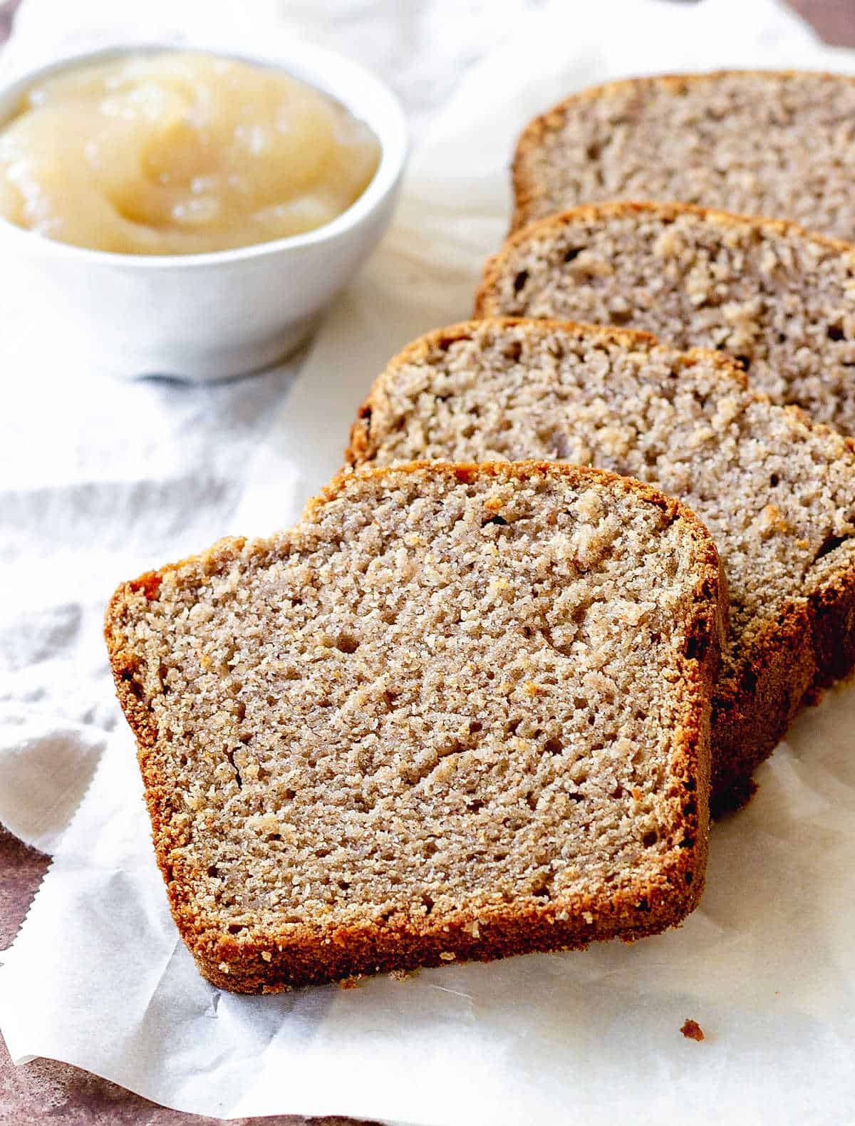 Slices of applesauce bread on white kitchen cloth, white bowl in back with applesauce