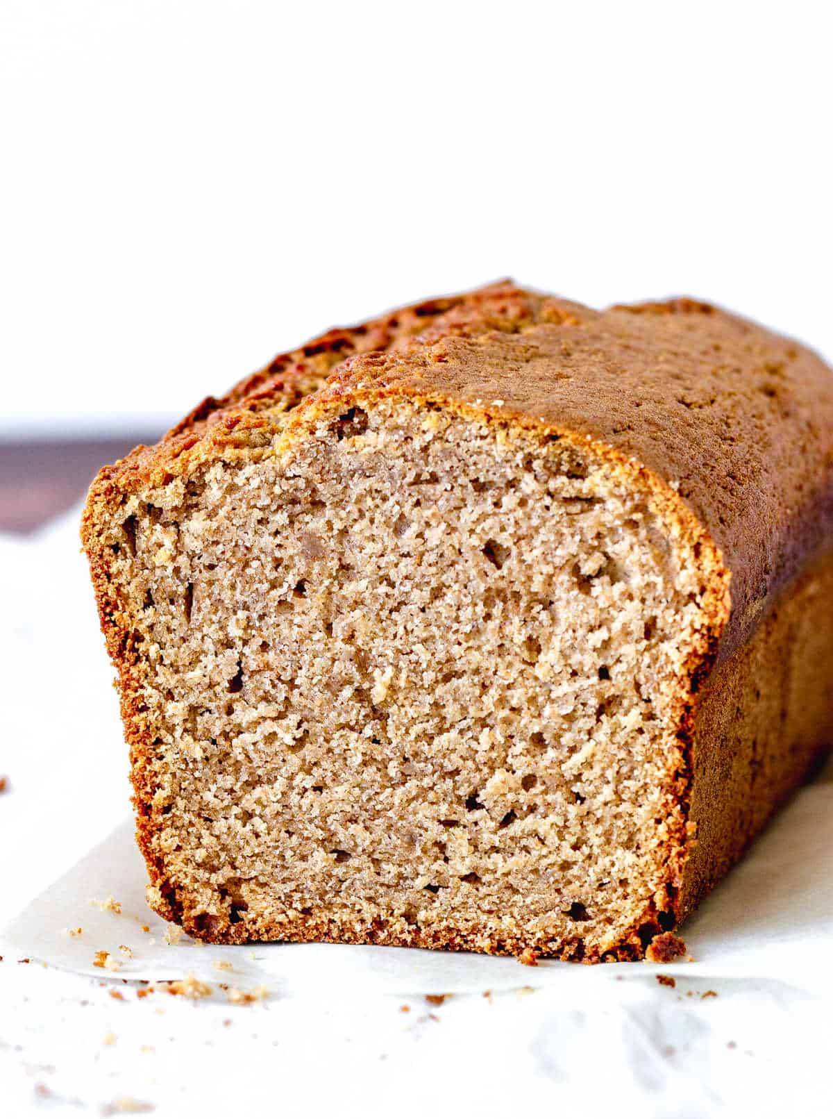Slanted view of cut applesauce bread on white surface and background