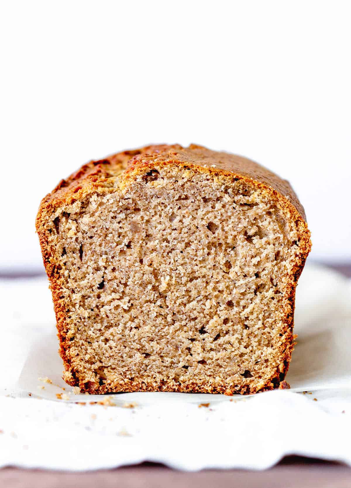 Half loaf of applesauce quick bread on white napkin, white background