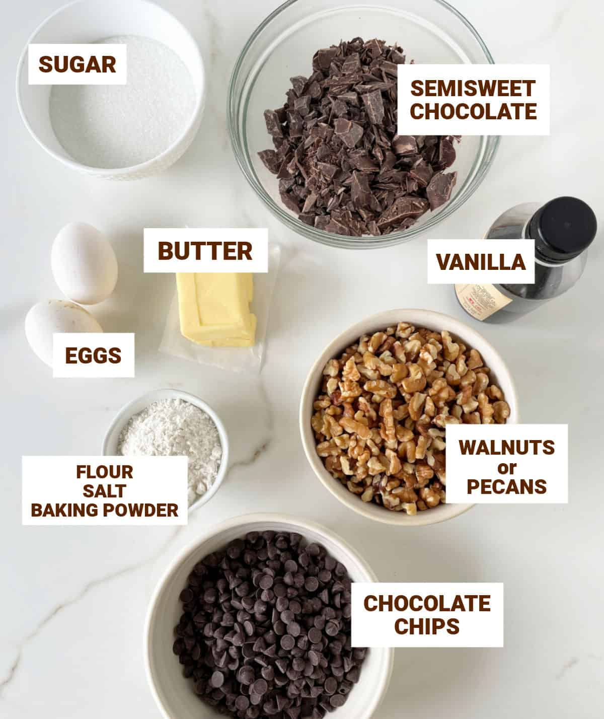 White surface with bowls containing ingredients for chocolate walnut cookies including butter, eggs, chopped chocolate and chips, vanilla
