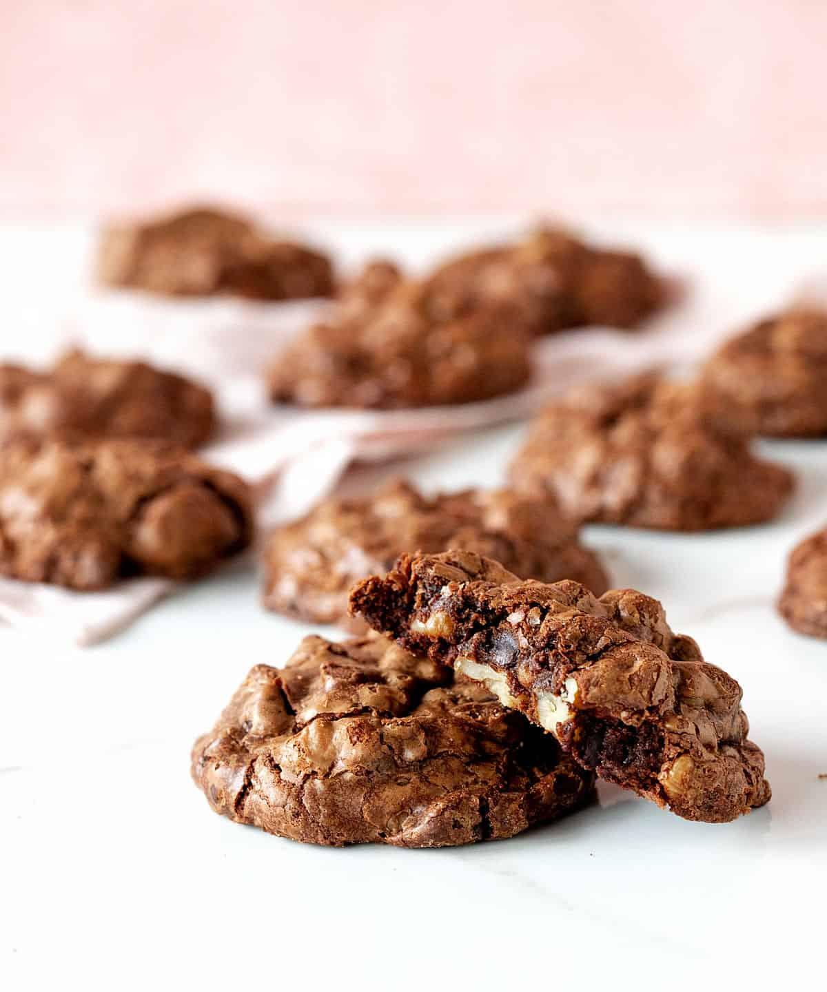 Several chocolate cookies, one bitter, on white and pink surface