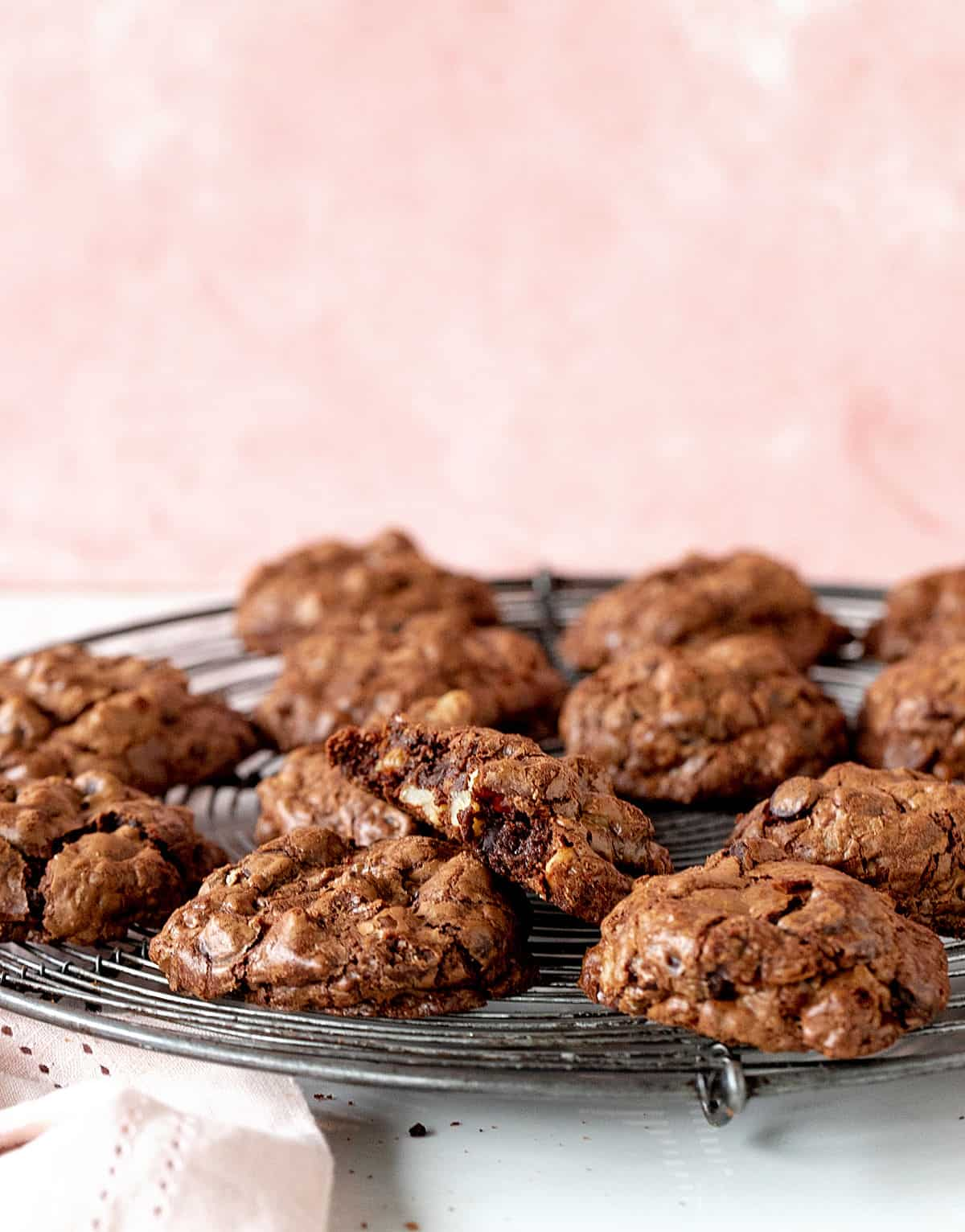 Pink background with chocolate cookies on wire rack