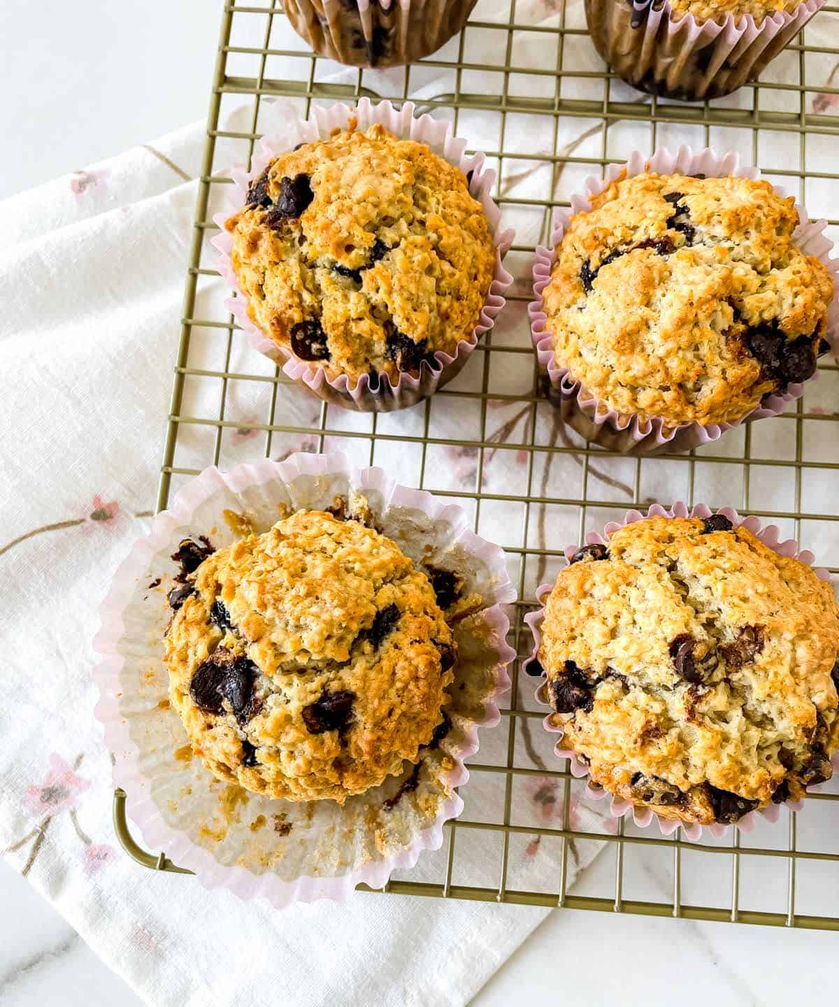 Four muffins with chips on wire rack, white kitchen towel
