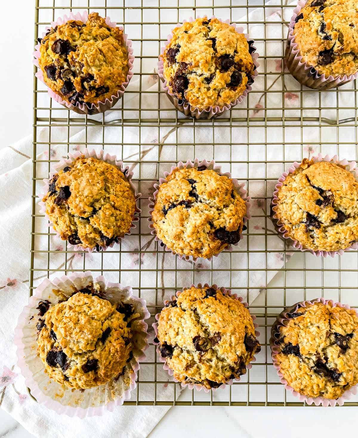 Top view of several oatmeal chocolate chip muffins on a cooling rack over a kitchen towel