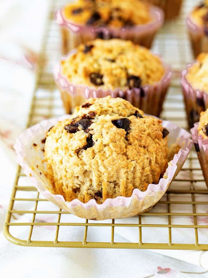 Oatmeal muffins with chips on paper liners on wire rack