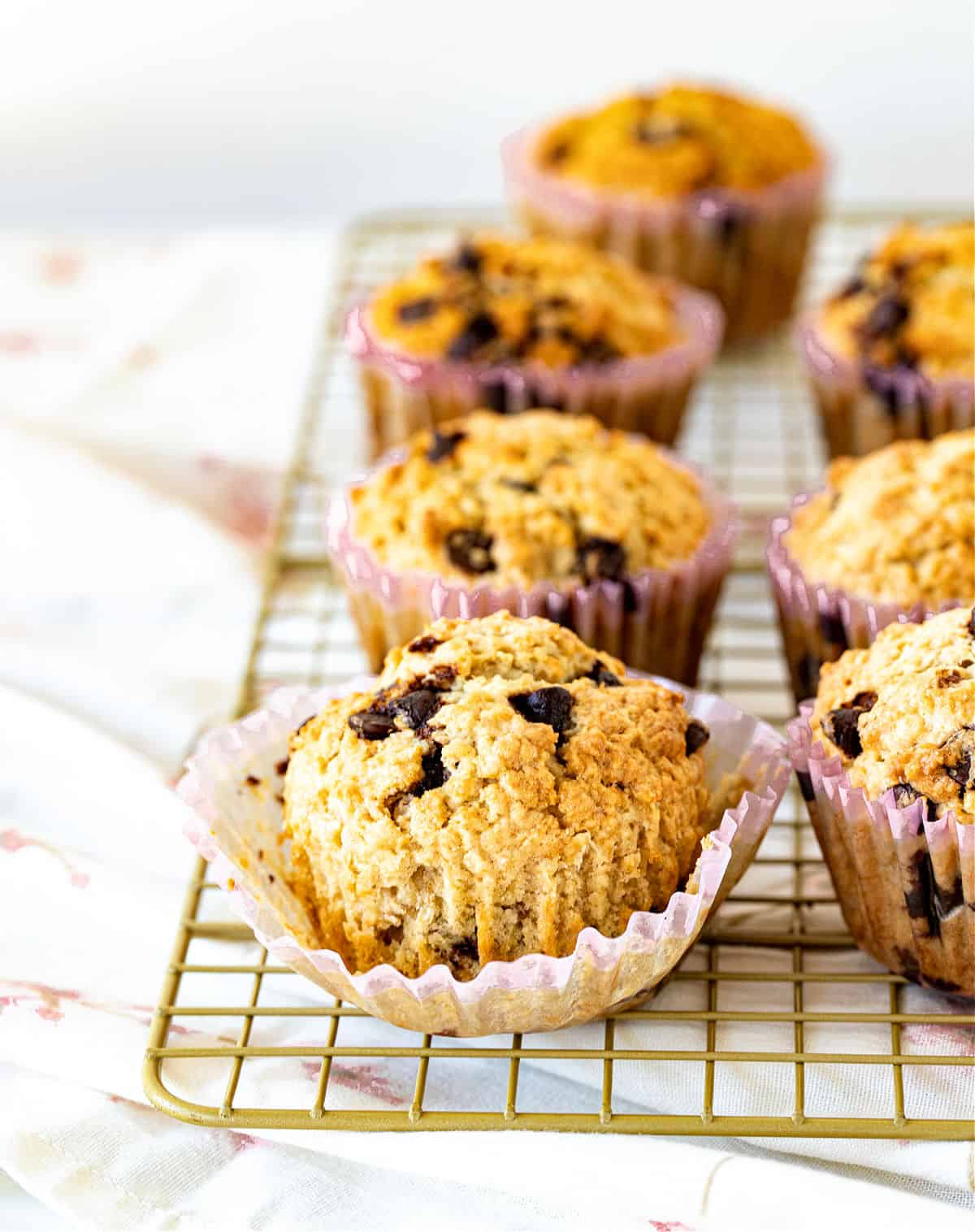 Rows of oatmeal chocolate chip muffins on golden wire rack