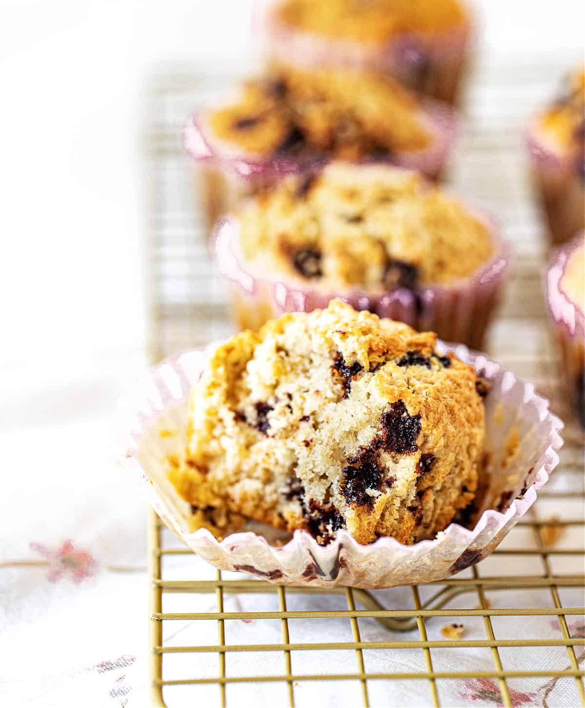 Eaten and whole muffins with chocolate chips on cooling rack