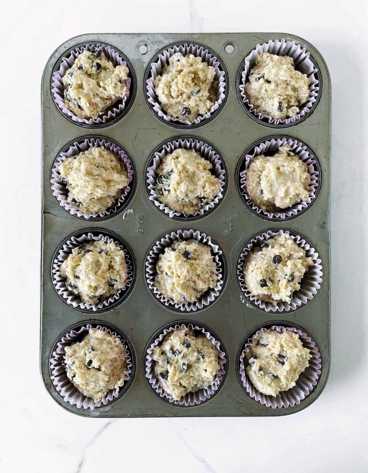 Top view of metal muffin pan with unbaked oatmeal muffins, white surface