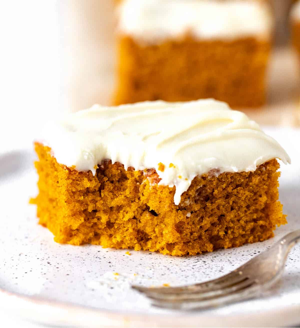 Bitten square of frosted pumpkin cake on white plate with fork, more cake on white background