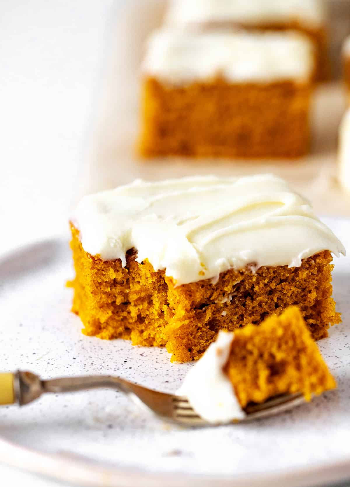 Fork with piece of pumpkin cake on white plate with eaten cake square, more on white background