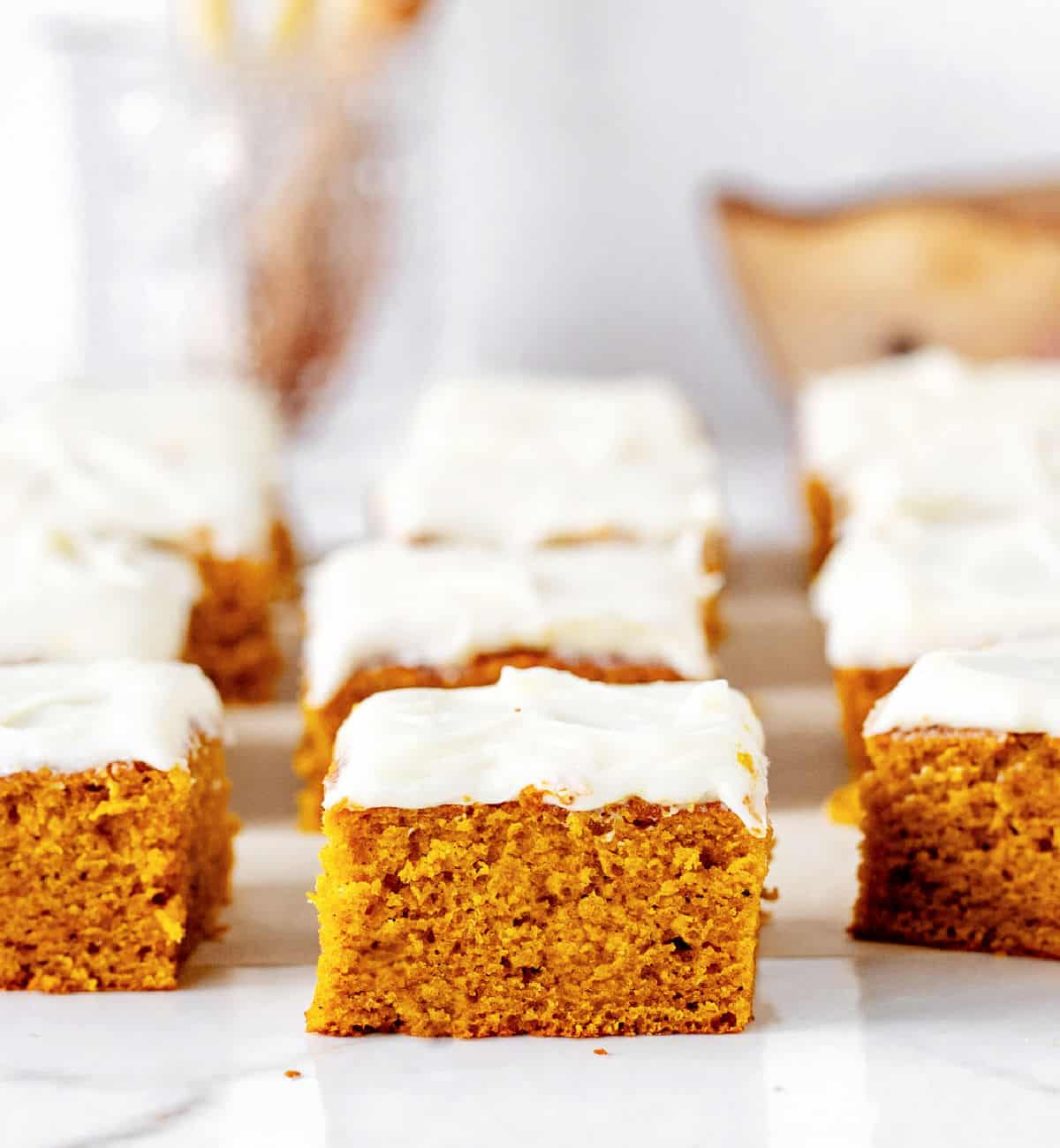 Squares of pumpkin cake with cream cheese frosting on white surface