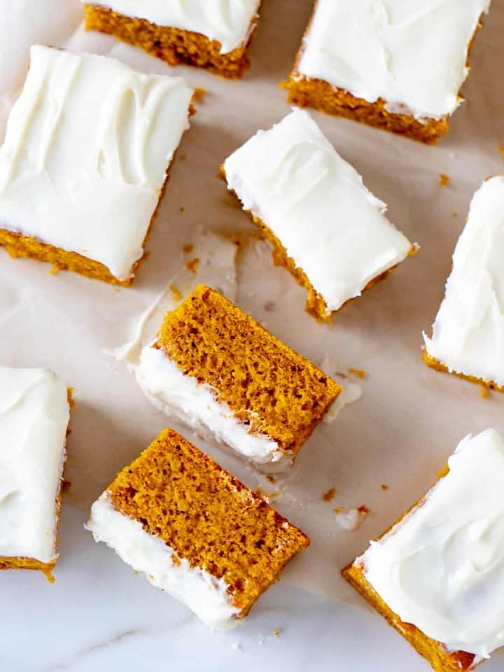 Cenital view of frosted pumpkin cake on parchment paper