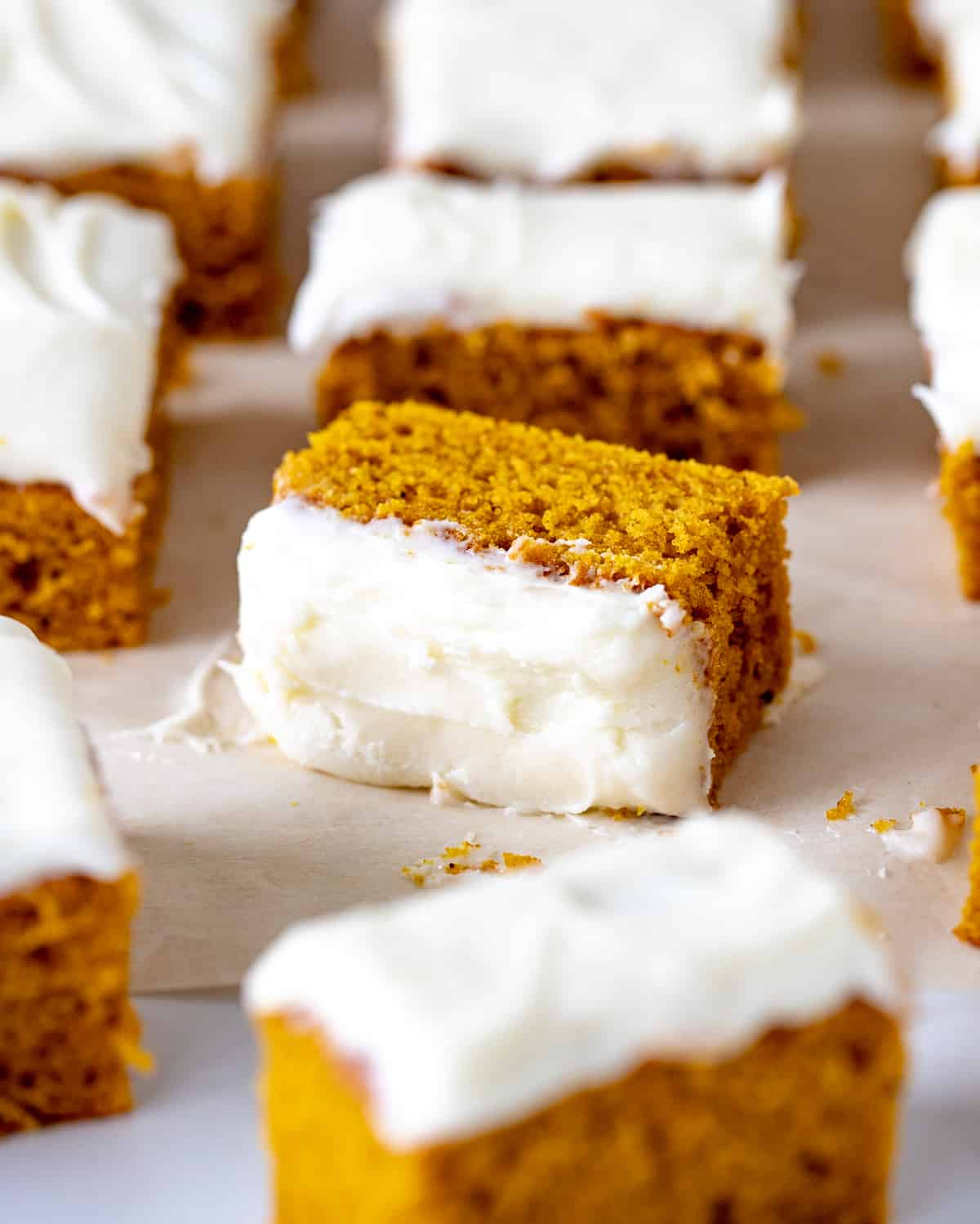 Several pieces of pumpkin sheet cake with cream cheese frosting on white surface
