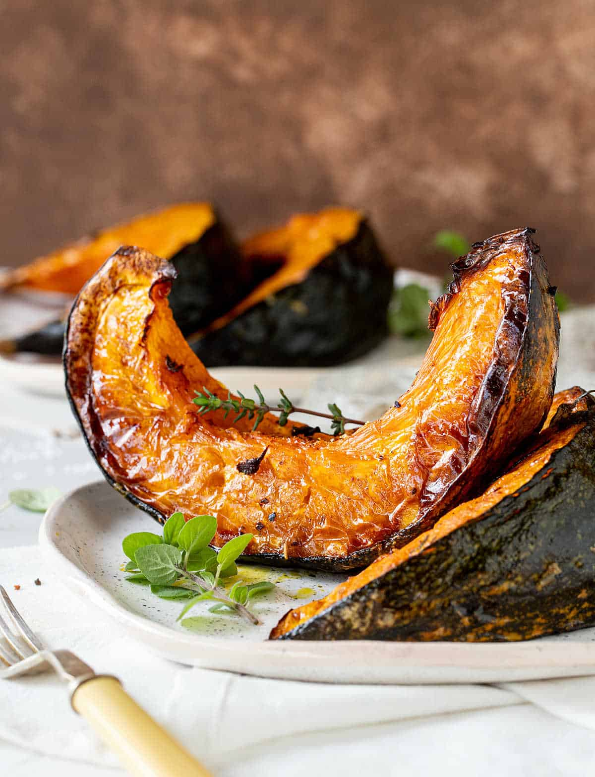 Brown background, white surface, plates containing blistered pumpkin wedges, fresh herbs
