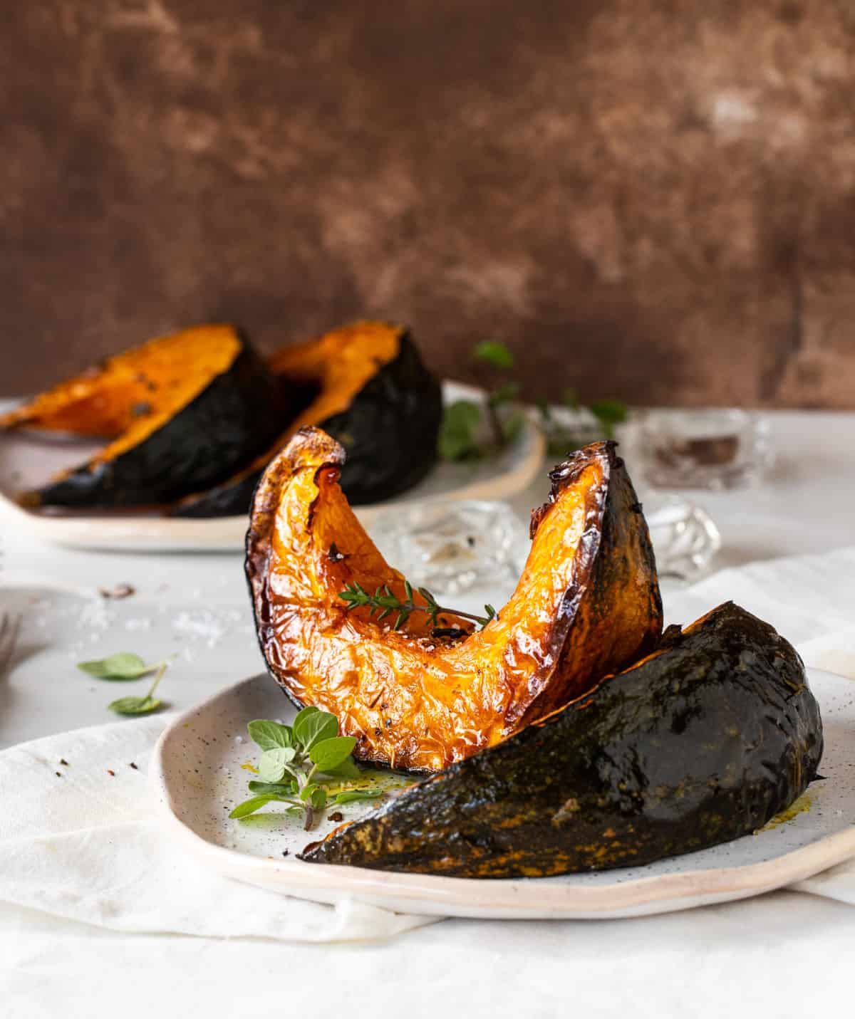 Baked pumpkin wedges with herbs on white plates, white surface, brown background