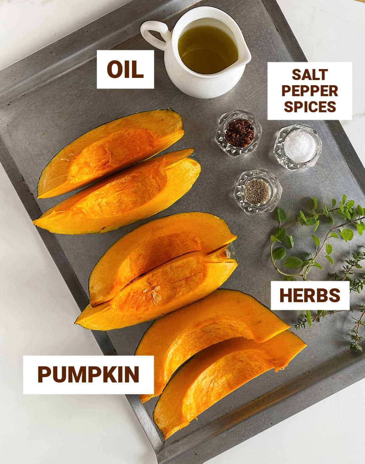 Metal baking sheet with pumpkin wedges, spices, jar with oil, herbs