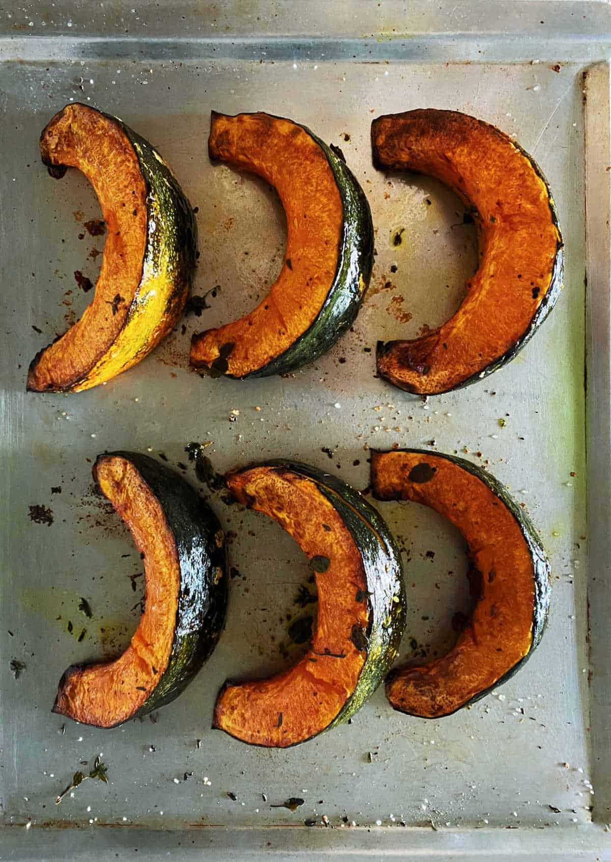 Six baked pumpkin wedges on metal baking sheet