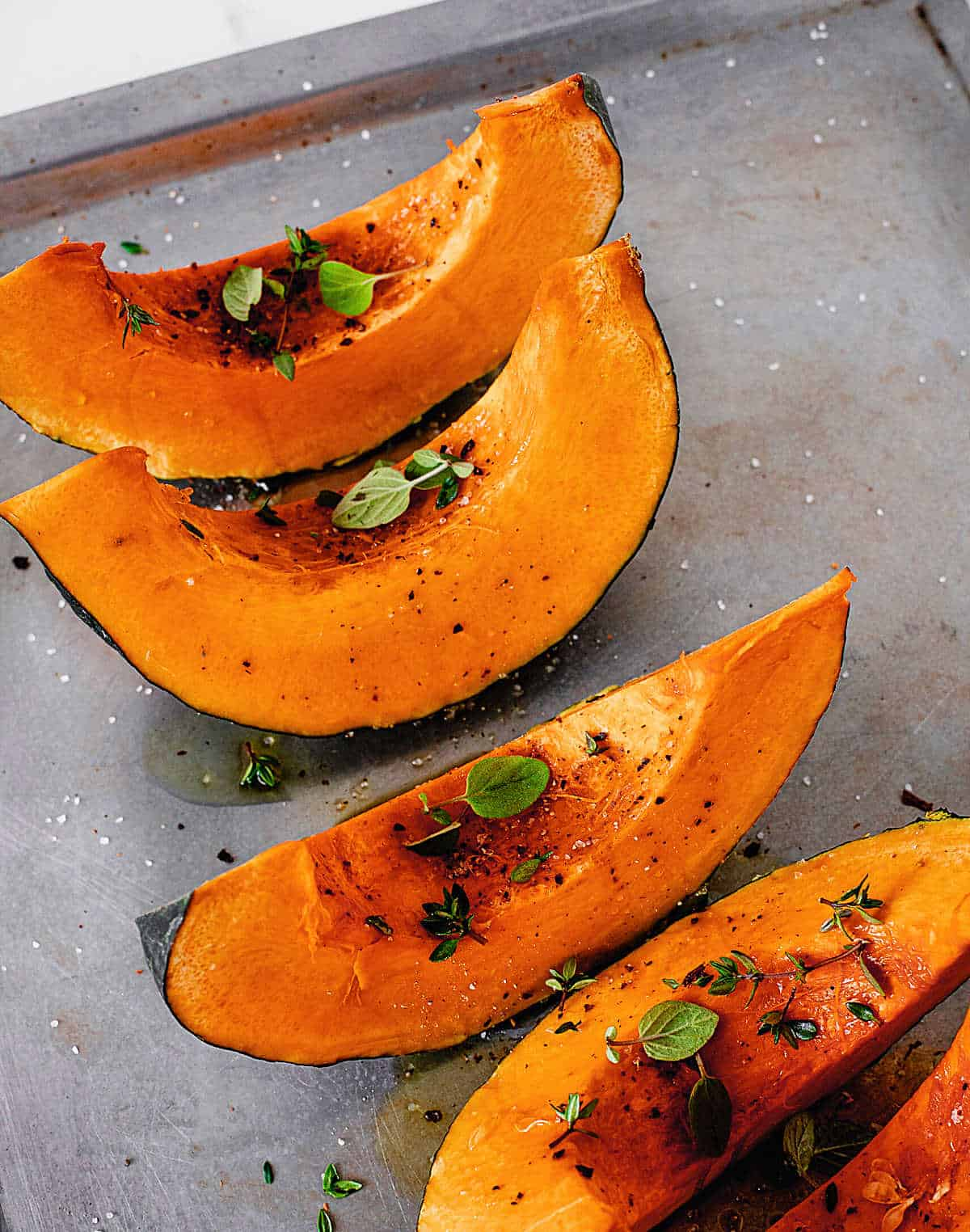 Raw pumpkin wedges with spices and herbs on metal baking sheet