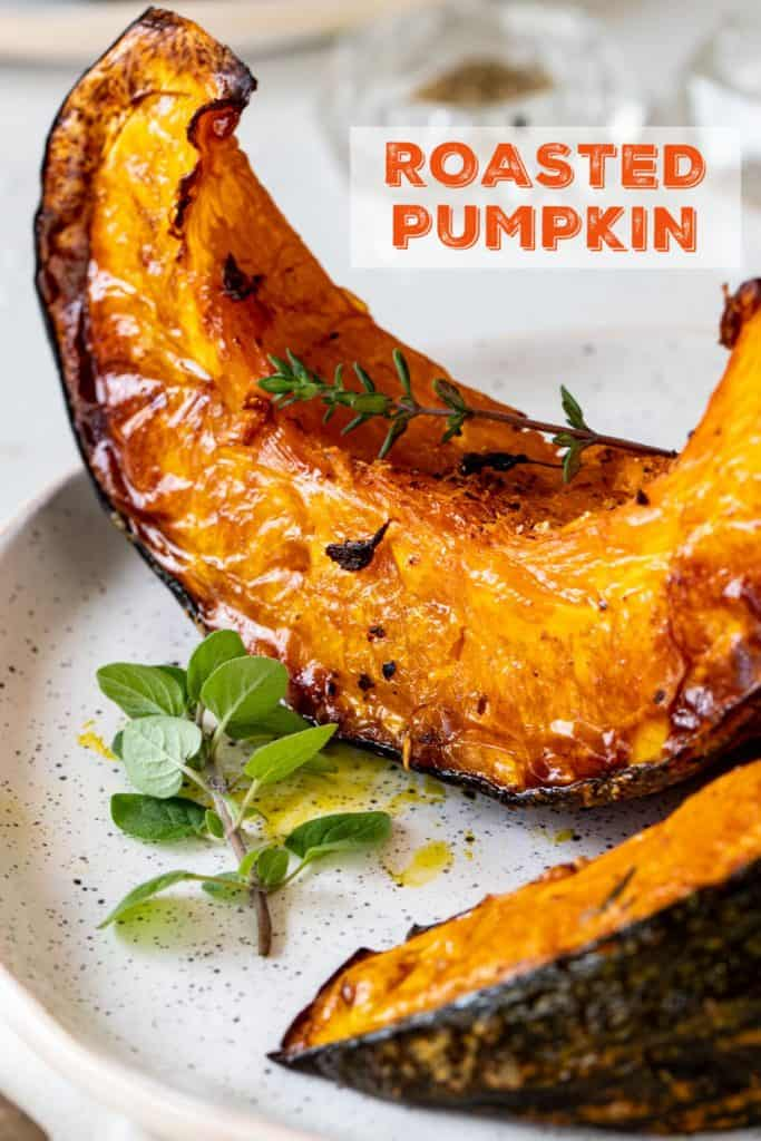 Close up of roasted pumpkin wedges on white plate, herbs, orange text overlay