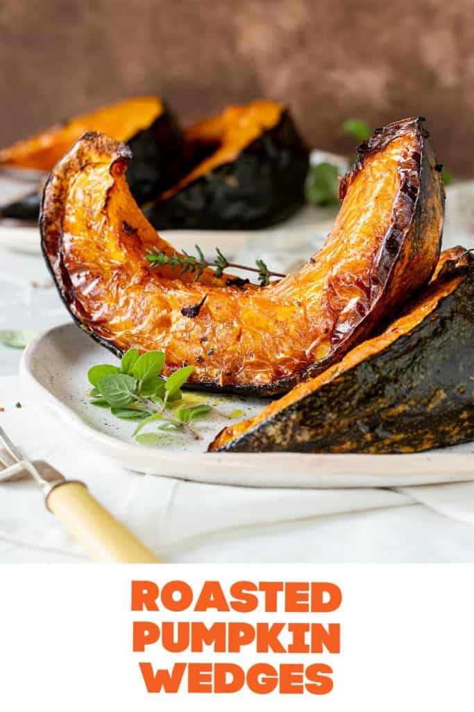 Roasted pumpkin wedges on white surface, brown background, herbs, fork, orange text overlay