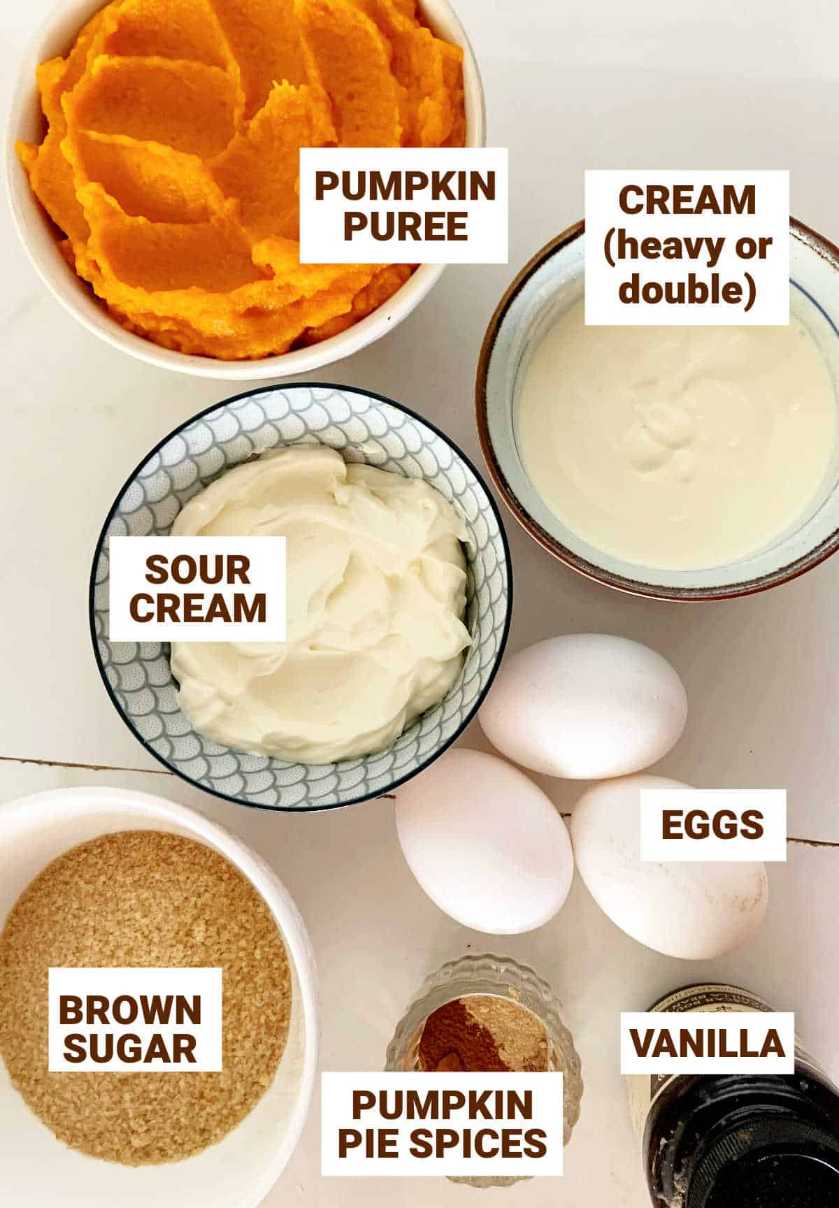 White surface with bowls containing ingredients for pumpkin pie with sour cream and brown sugar