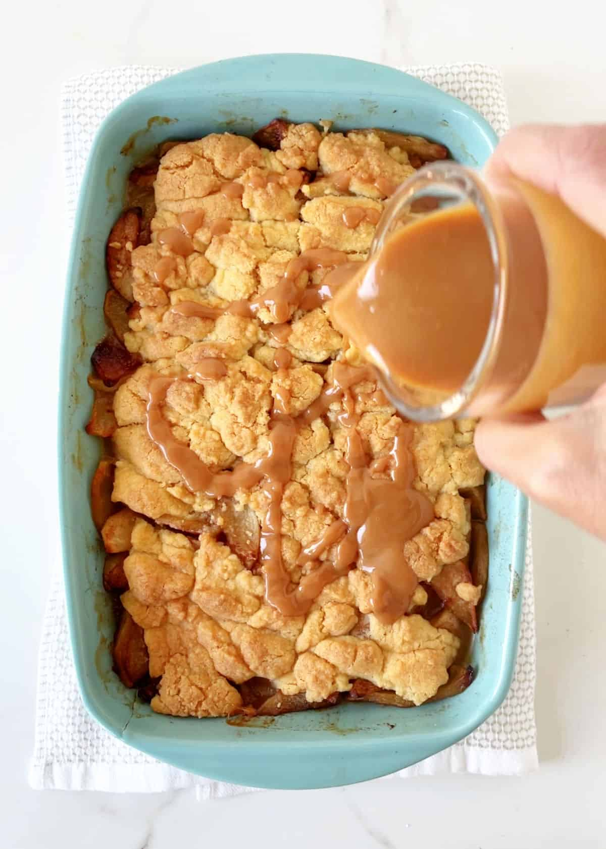 Drizzling caramel over baked dump cake in blue dish on towel over white marble surface