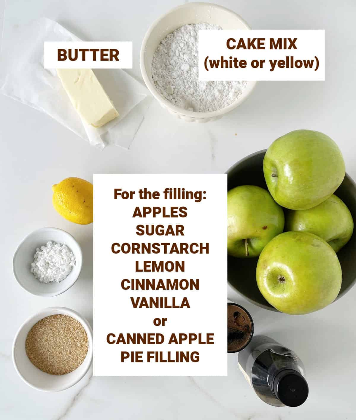 Ingredients for apple cake on white marble surface, including lemon, butter, spices, sugar, brown text overlay