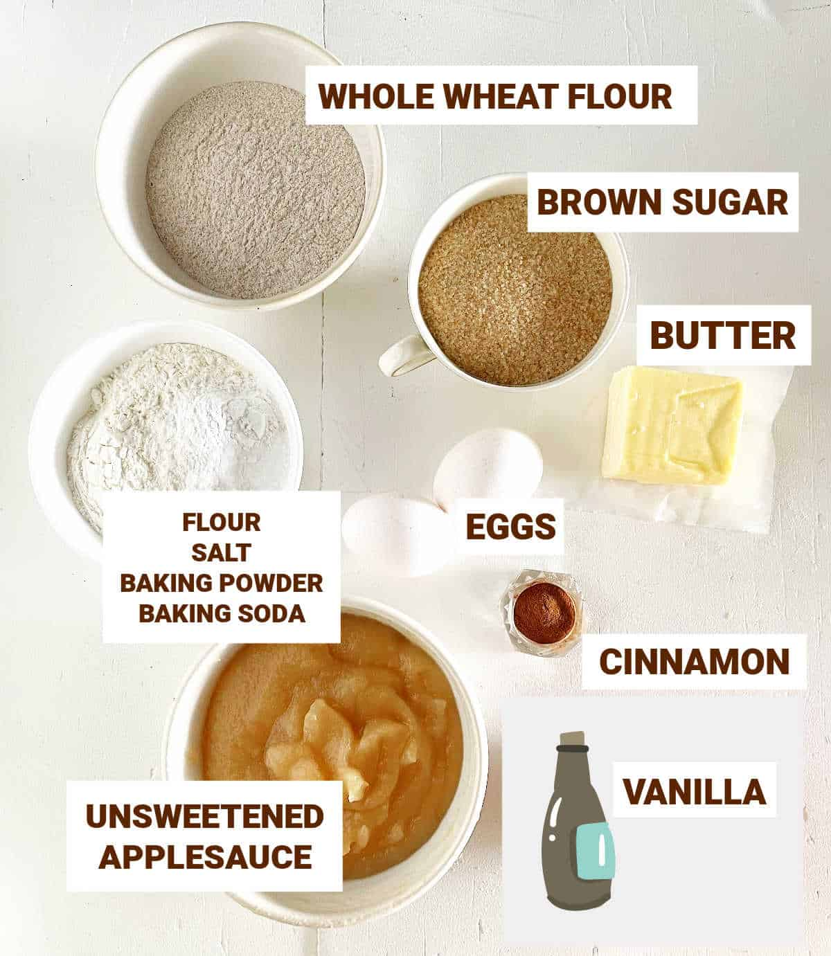 Bowls with ingredients for applesauce bread on white surface including butter, flours, brown sugar, eggs, cinnamon