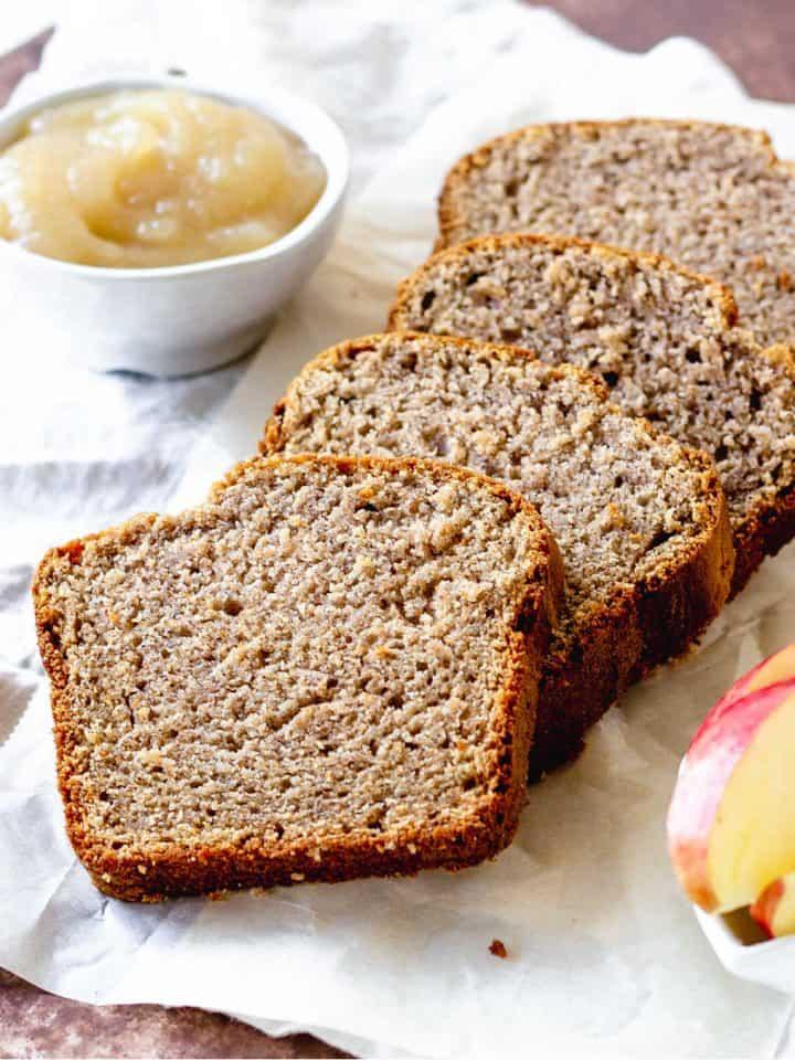 White napkin with slices of applesauce bread on top, applesauce in white bowl, fresh apple