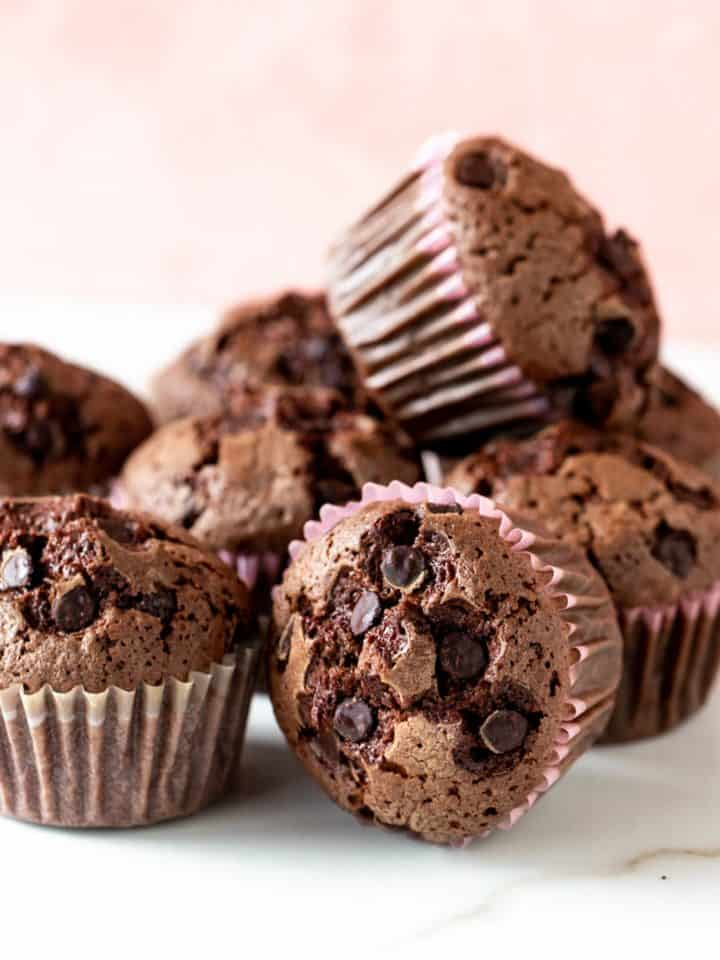 Close up of several chocolate muffins in a mound; white and pink background