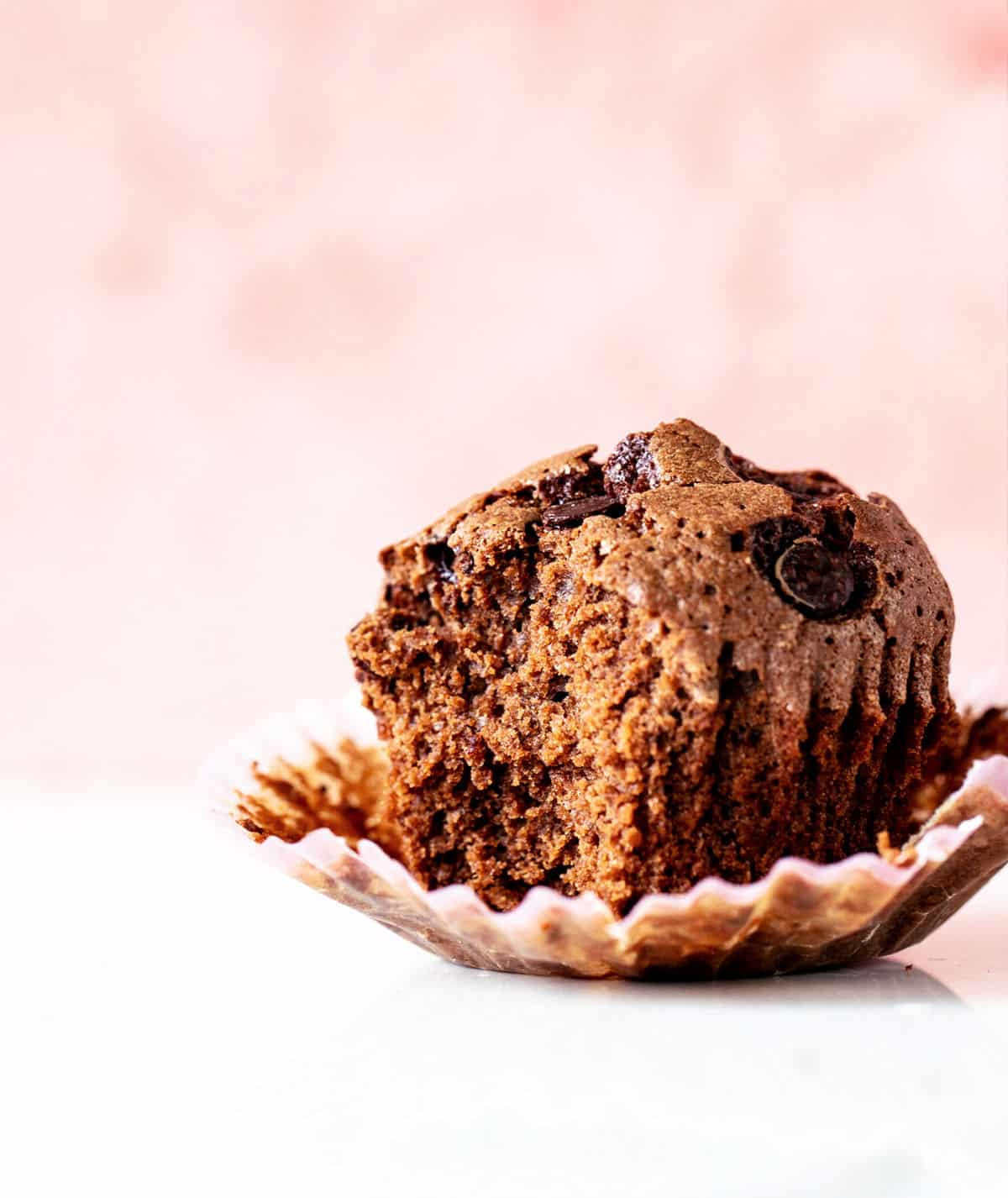 Eaten chocolate muffin in paper liner, white surface and pink background