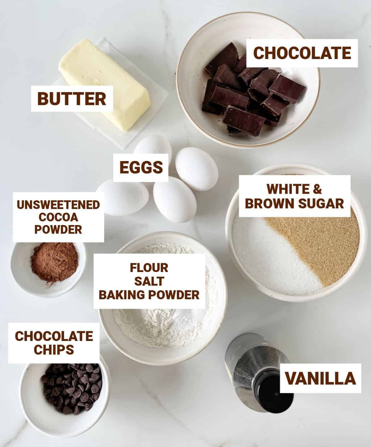 White marble with bowls containing ingredients for chocolate muffins including butter, vanilla, sugar, cocoa powder, chips, eggs