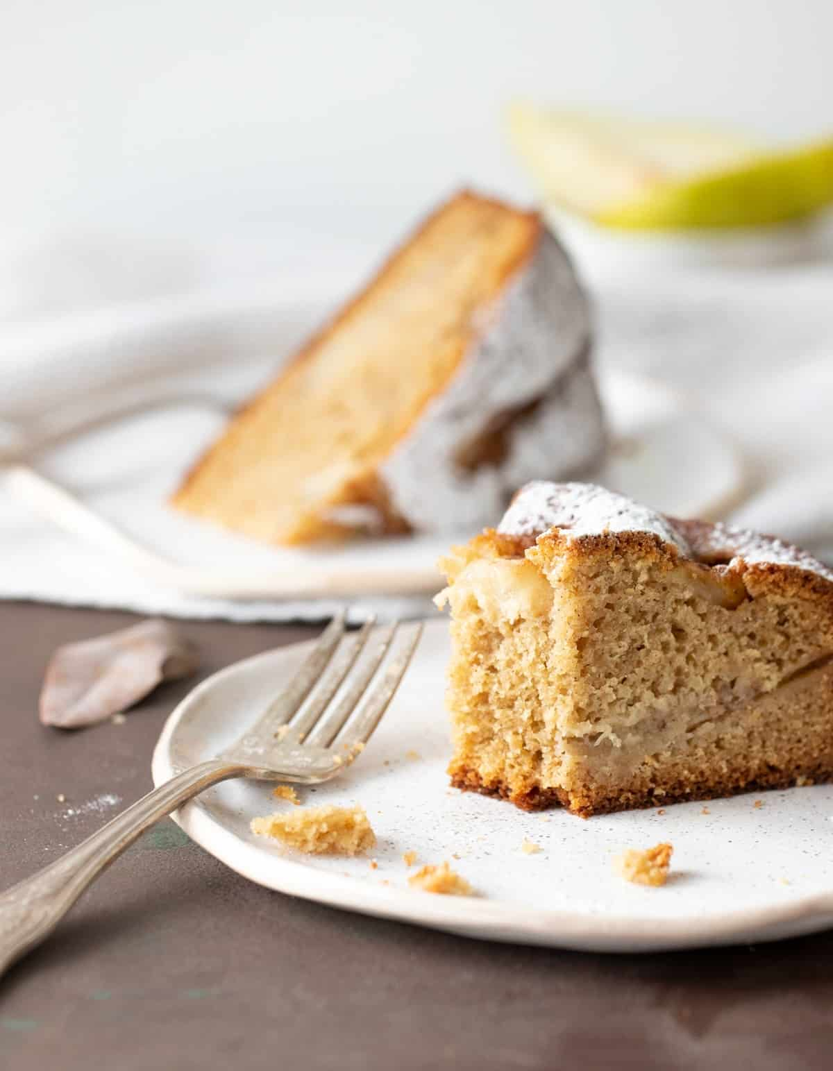 Eaten slice of pear cake on white plate, silver fork, dark surface, whole slice in background