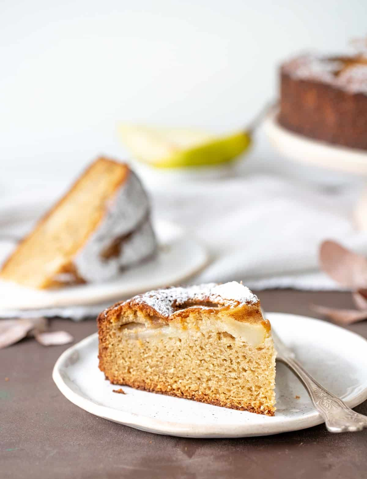 Slices of pear cake on white plates, brown surface, white background