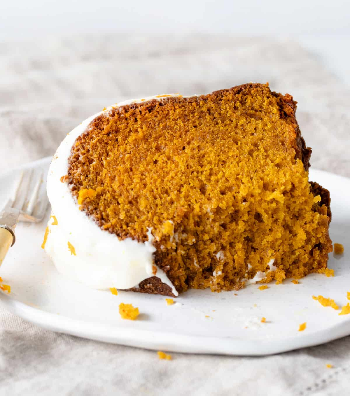 Eaten slice of frosted pumpkin cake on white plate, grey background