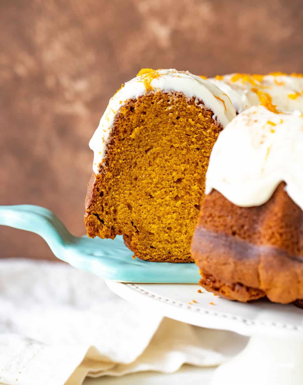 A slice of frosted pumpkin bundt cake on blue cake server, brown background, cake on stand