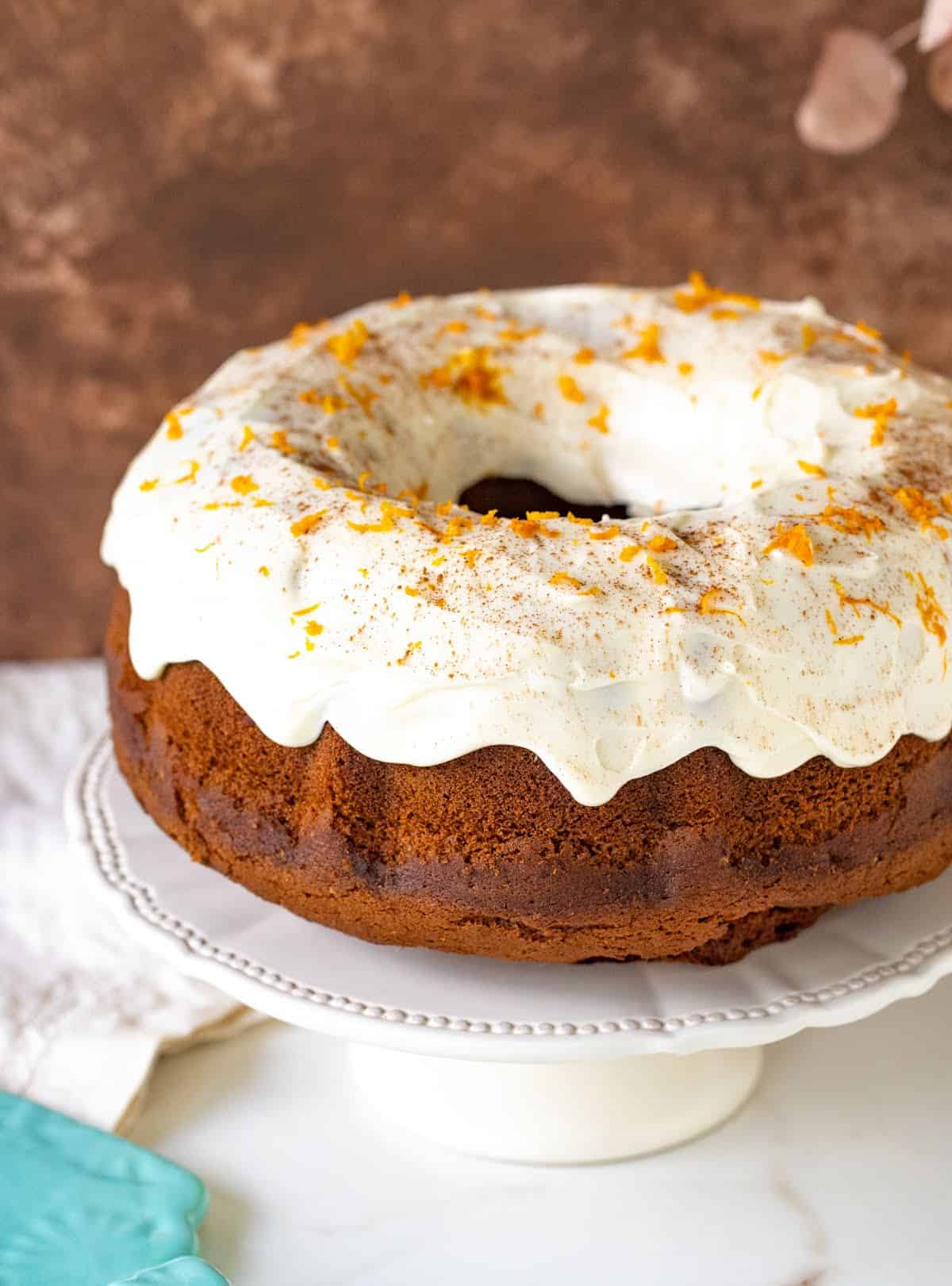 Whole frosted pumpkin bundt cake on white cake stand, white surface, brown background
