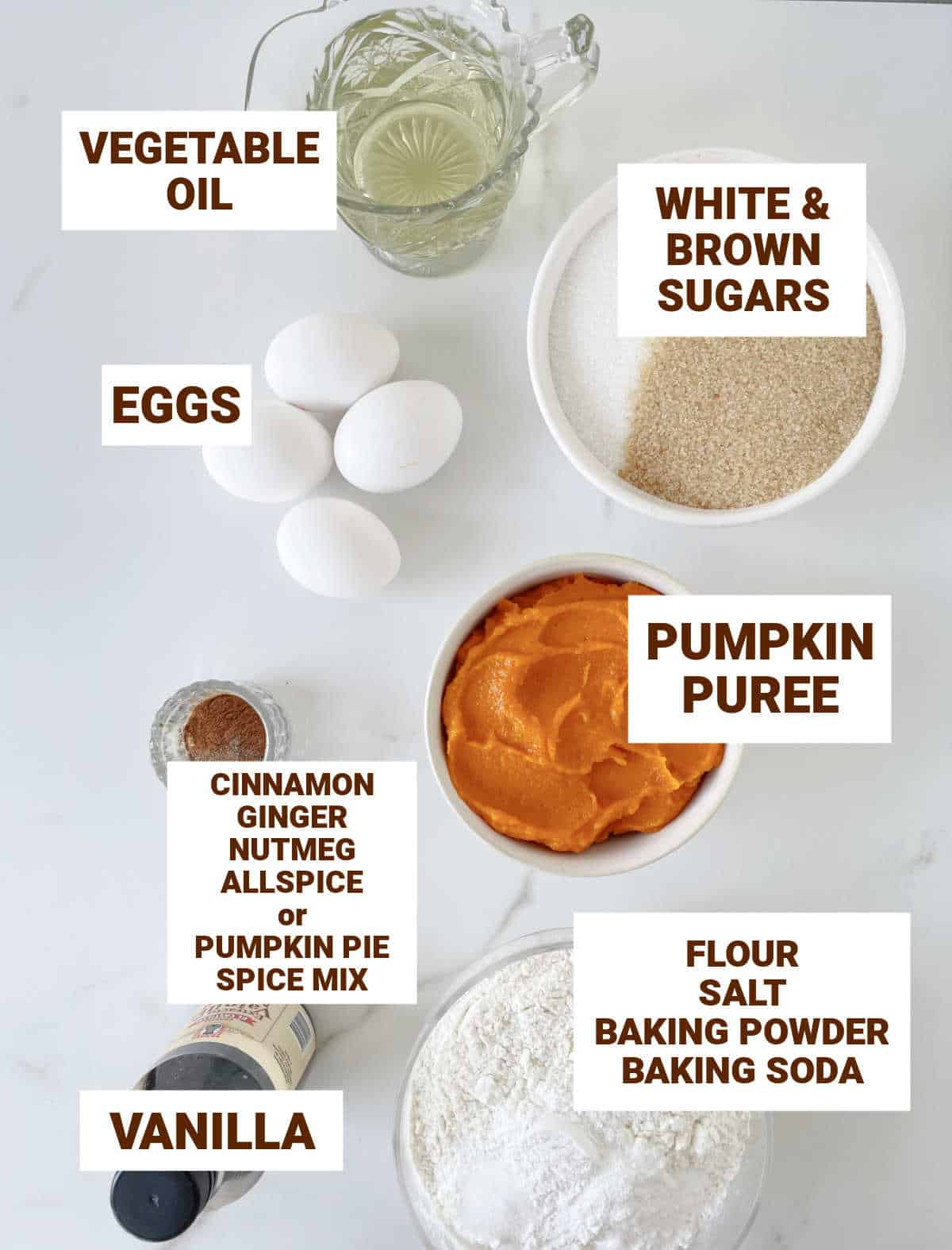Bowls on white surface with ingredients for pumpkin cake including vanilla, dry ingredients, oil, sugars, eggs