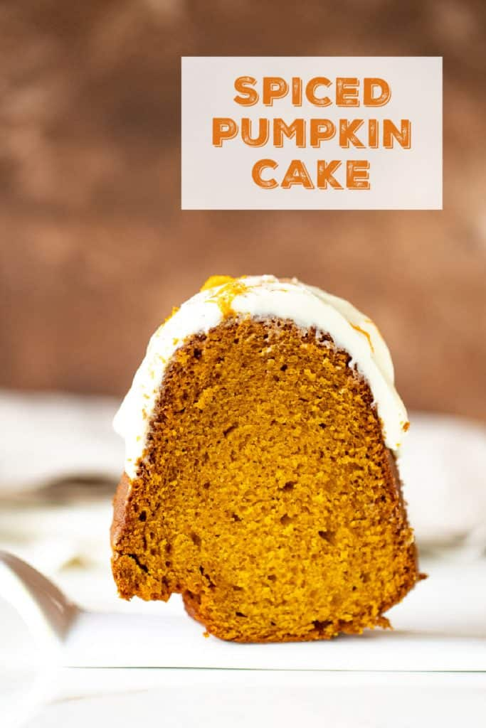 Slice of frosted pumpkin bundt cake on white cake server, brown background, orange text overlay